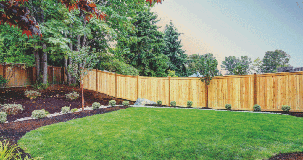 a-beautiful-wood-fence-around-a-property-backyard-of-a-home-with-beautiful-landscaping-as-well